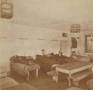 Grainy photo of a cramped prison hospital room with multiple beds and a table.