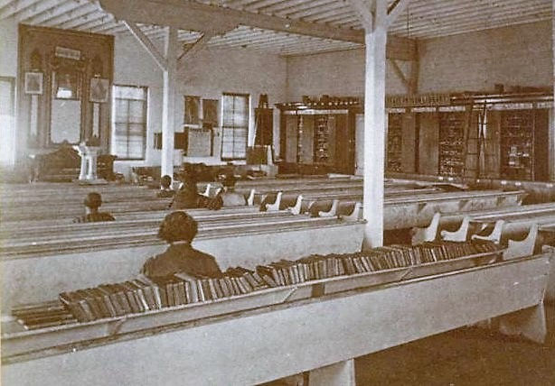 The San Quentin school was in the church. People sit in a prison's church pews with books around the walls.