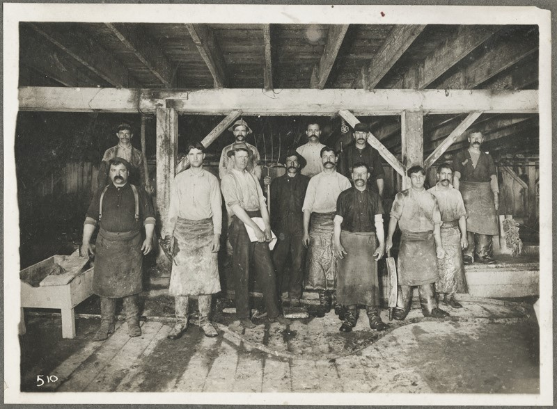 Men stand in wood building, their aprons are stained.