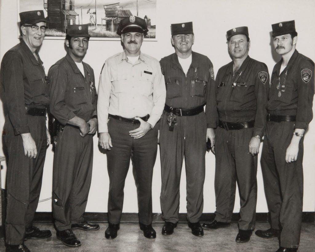 Six men in correctional uniforms.