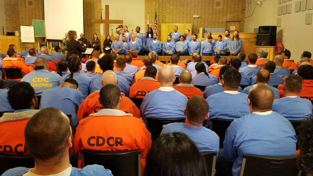Inmates sit in a chapel while other inmates form a choir.
