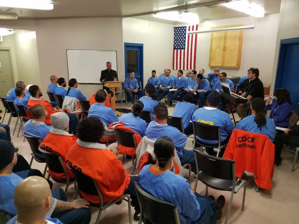 Inmates in orange and blue clothing listen to a chaplain speak.