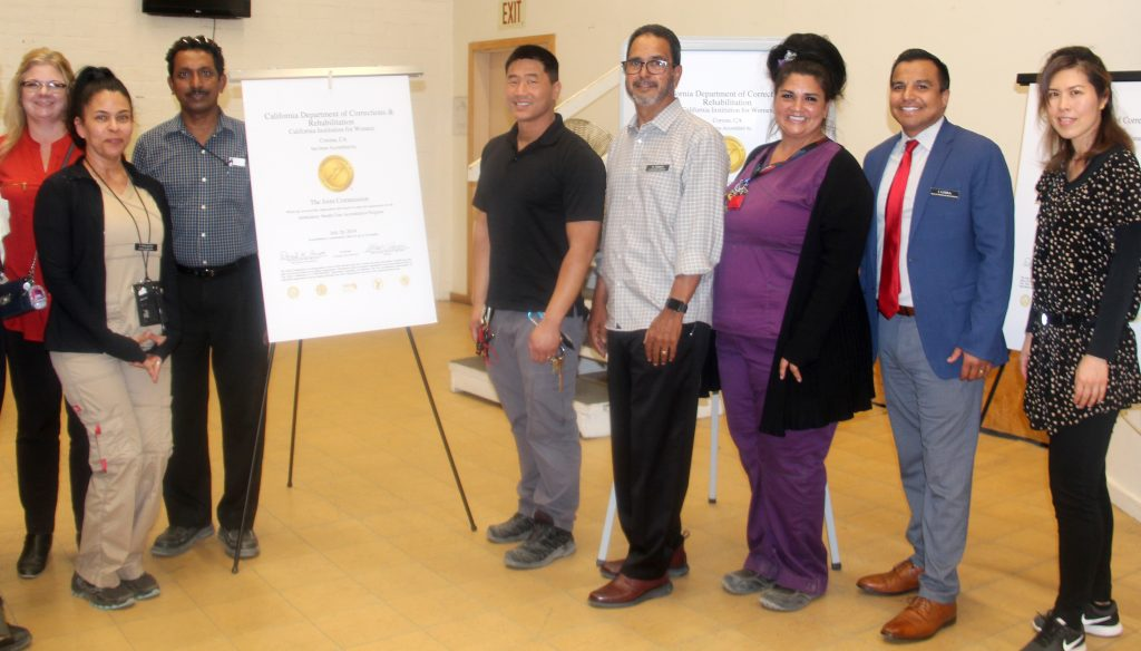 Group of eight people stand next to a poster for achieving accreditation at California Institution for Women.