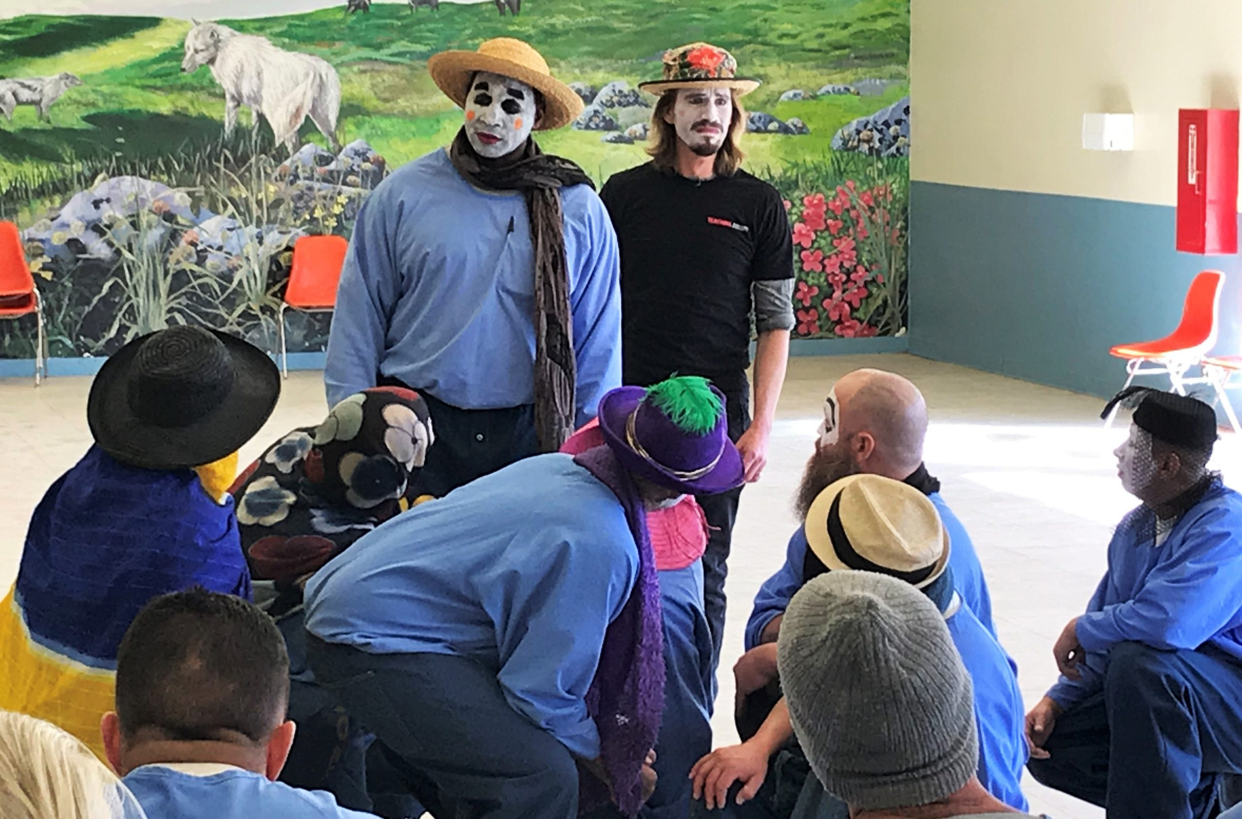 Prison inmates wear face paint and hats while rehearsing a scene.