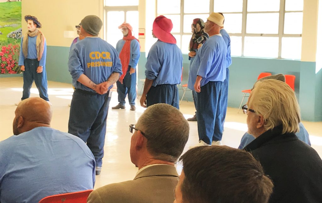 An audience watches inmate actors present a scene.