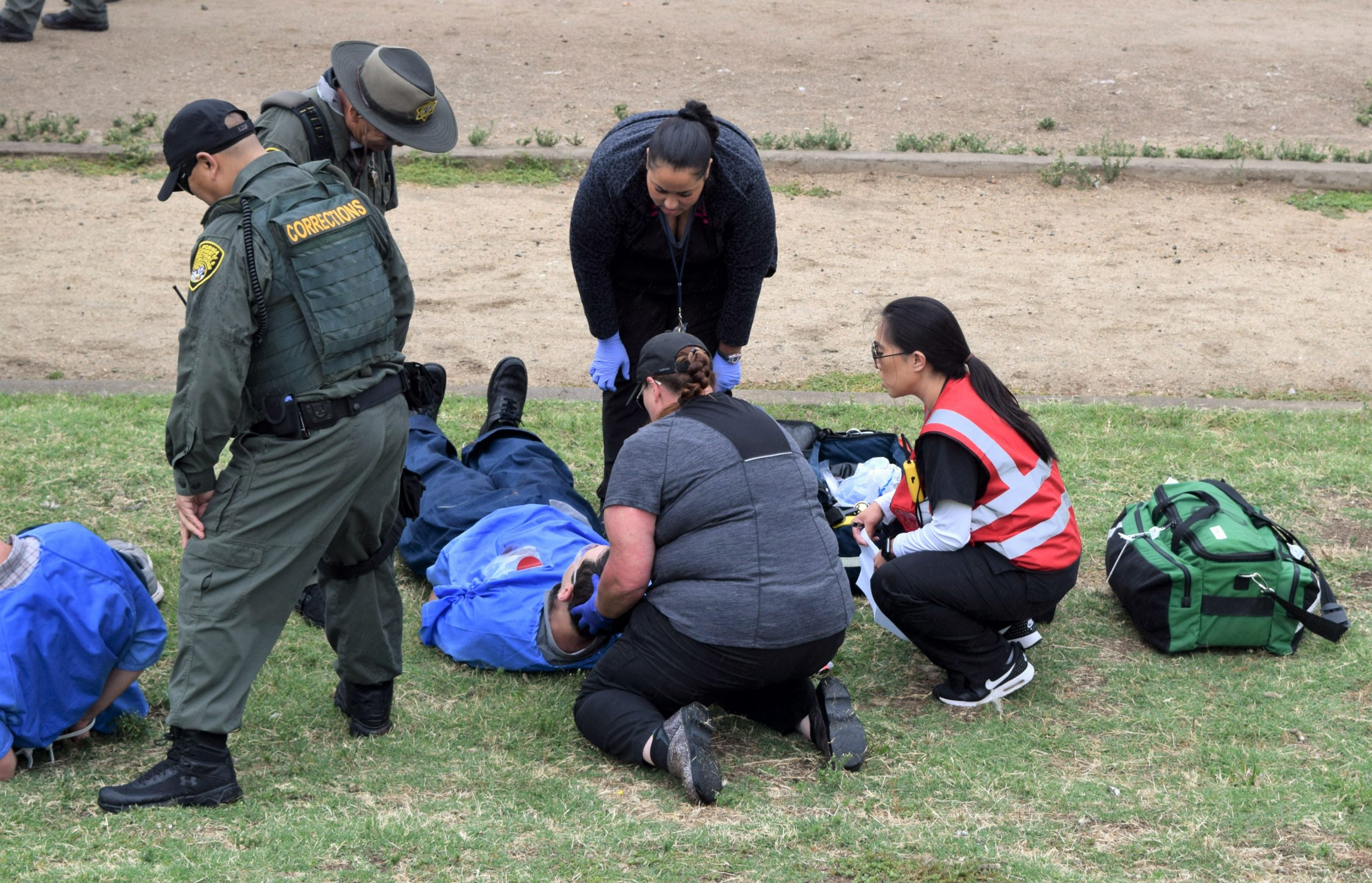 Prison medical staff huddle around a person on the ground while a correctional officer watches.