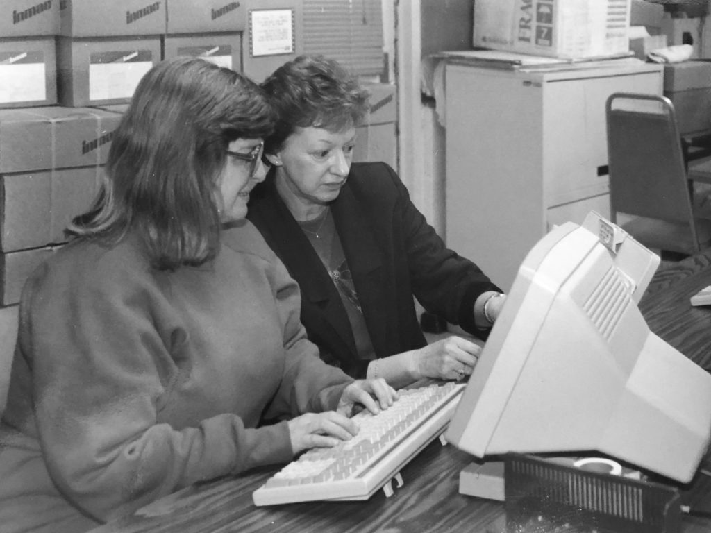 An inmate works on a computer while an instructor assists.