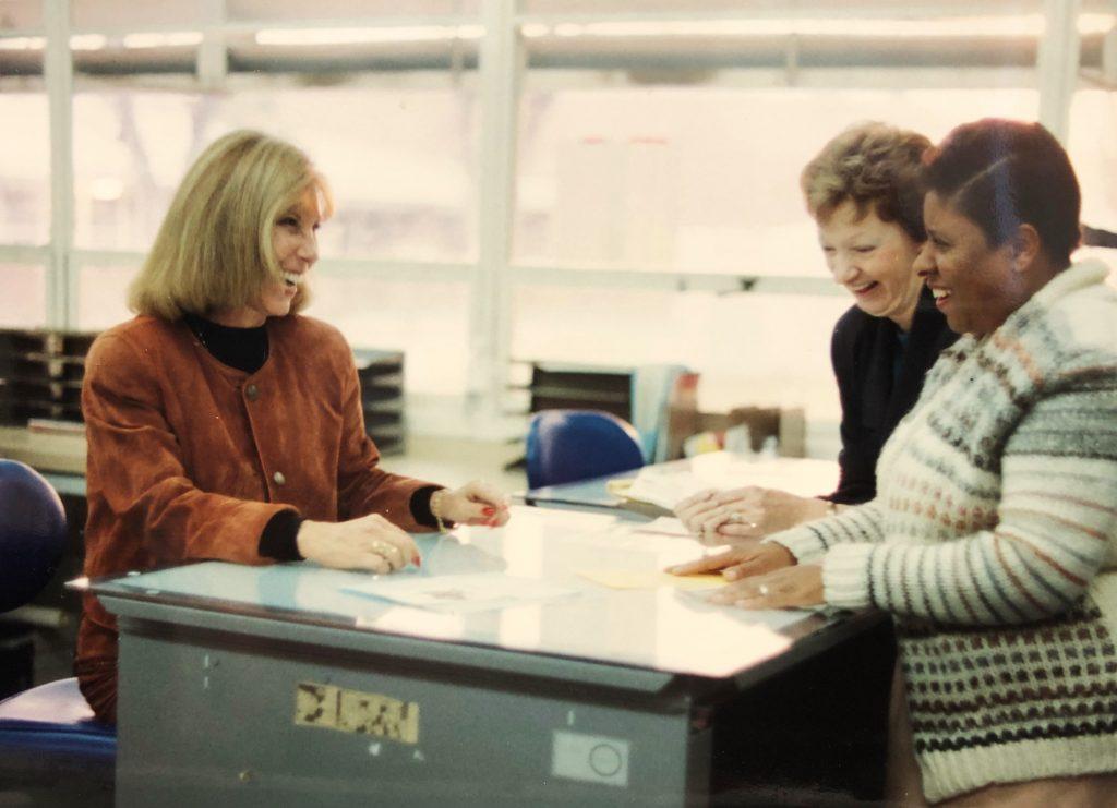 Three women stand around a work desk smiling.
