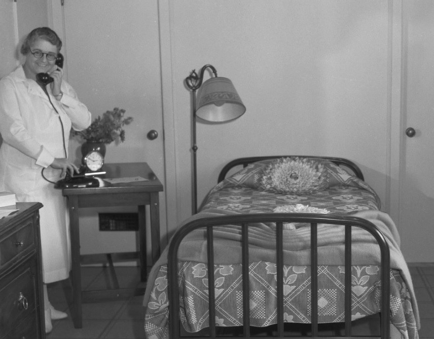 Prison matron holds a telephone in a women's prison.