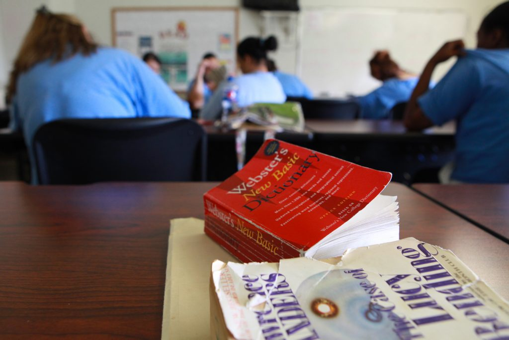 Books can be seen in the foreground while inmates study in a classroom.