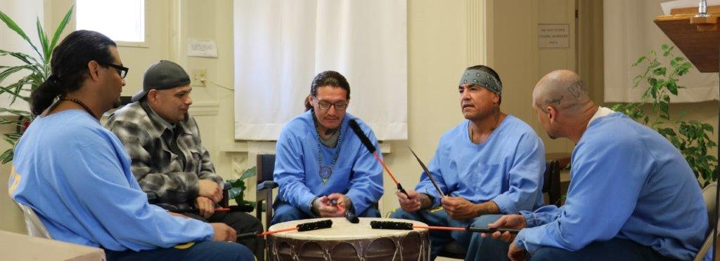 A Native American Spiritual Adviser and four inmates pound a drum at California Men's Colony.
