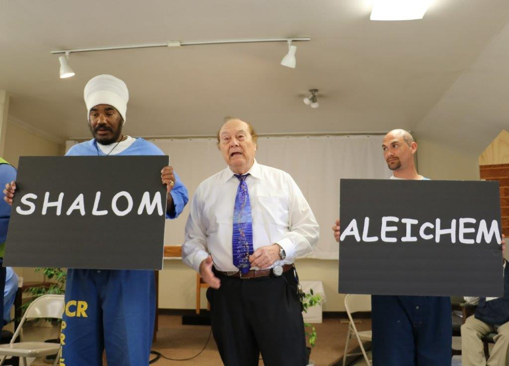 Two inmates hold signs showing different greetings. They are standing beside a rabbi at California Men's Colony.
