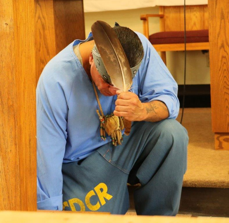 Native American prison inmate prays using an eagle feather.