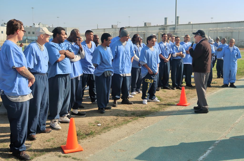 Corcoan state prison inmates stand in a yard listening to a man speak.
