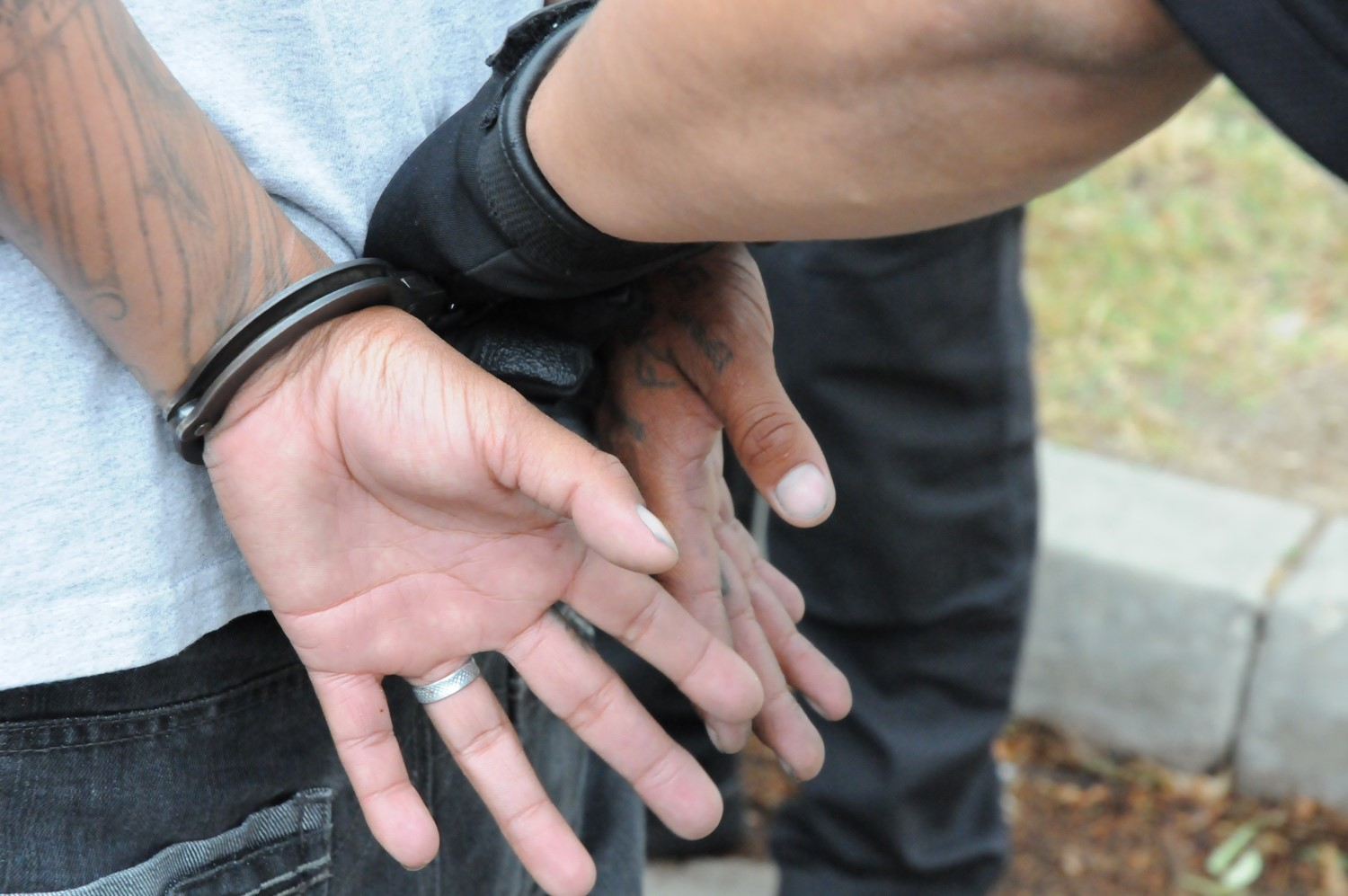An officer puts handcuffs on a man.