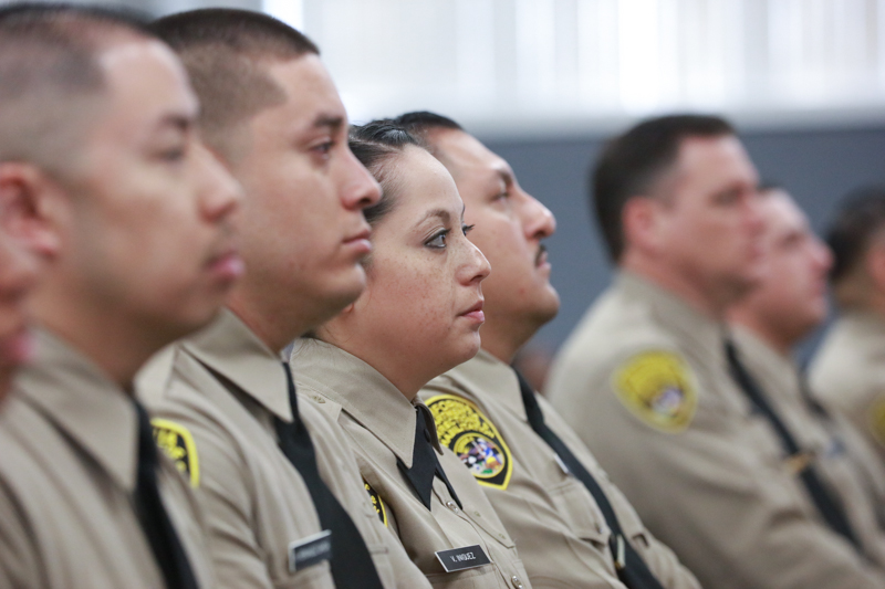 Men and women in correctional officer uniforms.