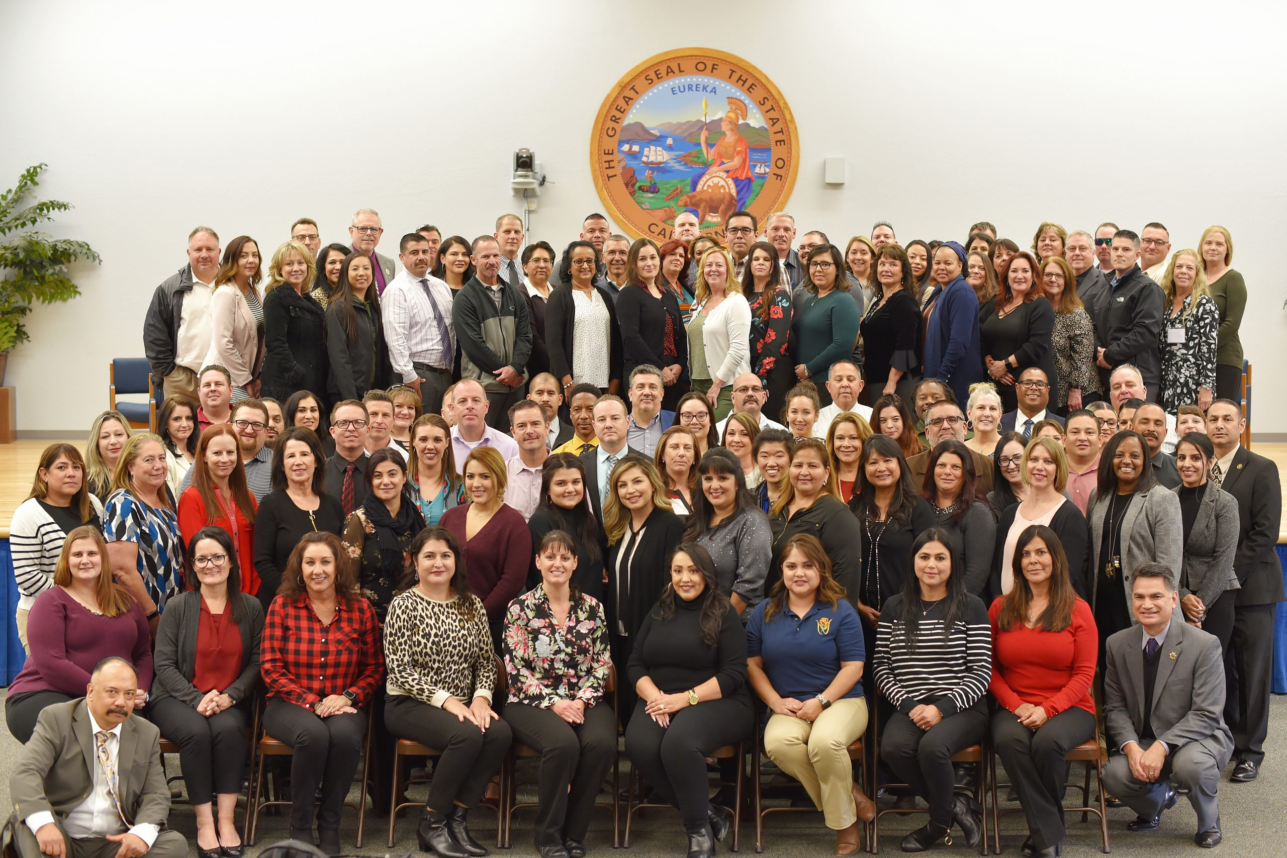 Large group of people pose in front of the California State Seal.
