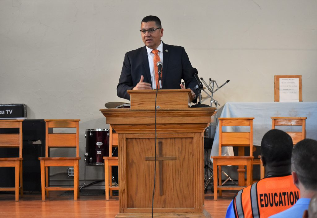 CDCR Secretary Ralph Diaz speaks to inmates from a lectern at Folsom State Prison.