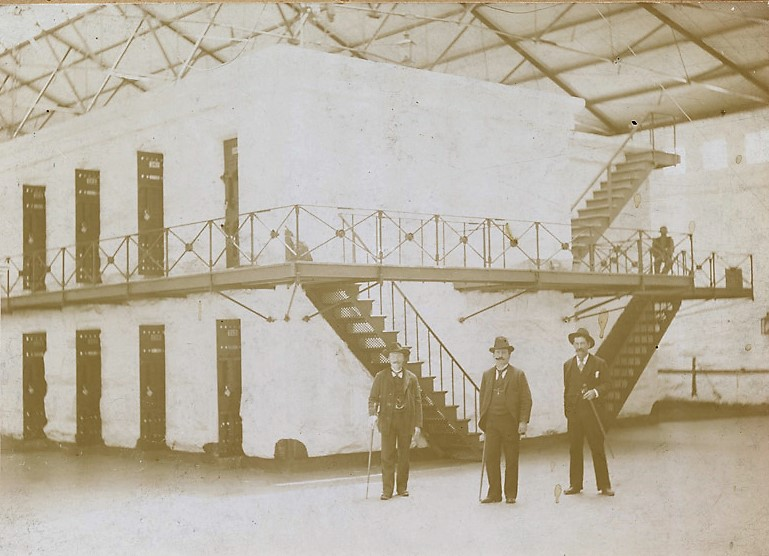 Prison staff in grainy antique photo stand beside prison cell blocks in 1890s.