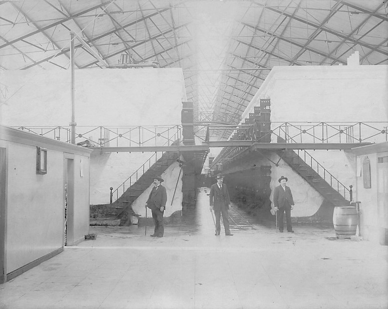Three prison staff members stand by two cell block buildings in Folsom Prison.