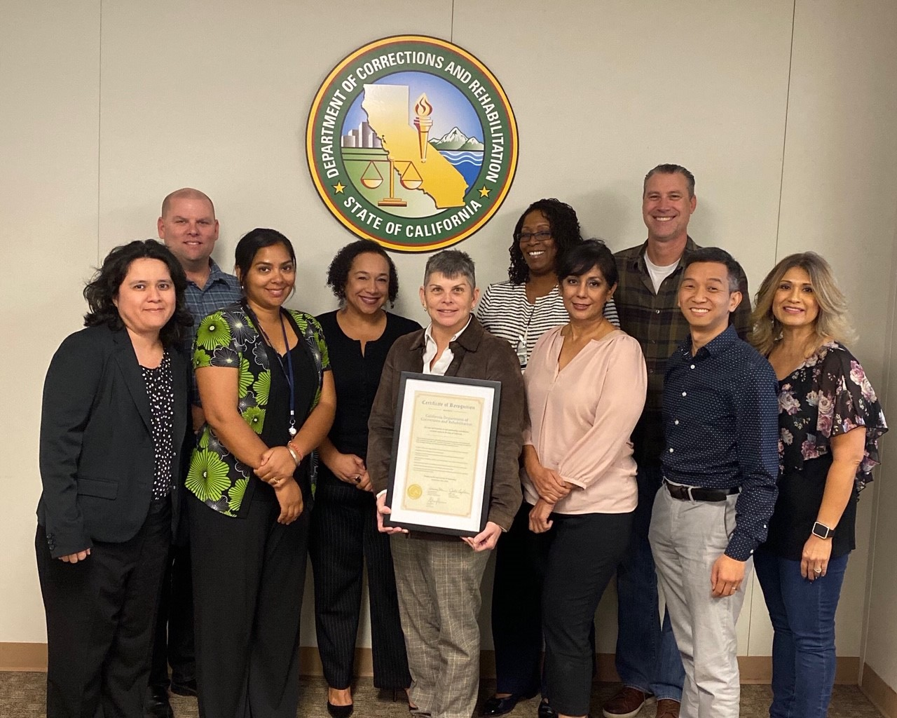 Men and women stand under a CDCR logo while holding a framed certificate.