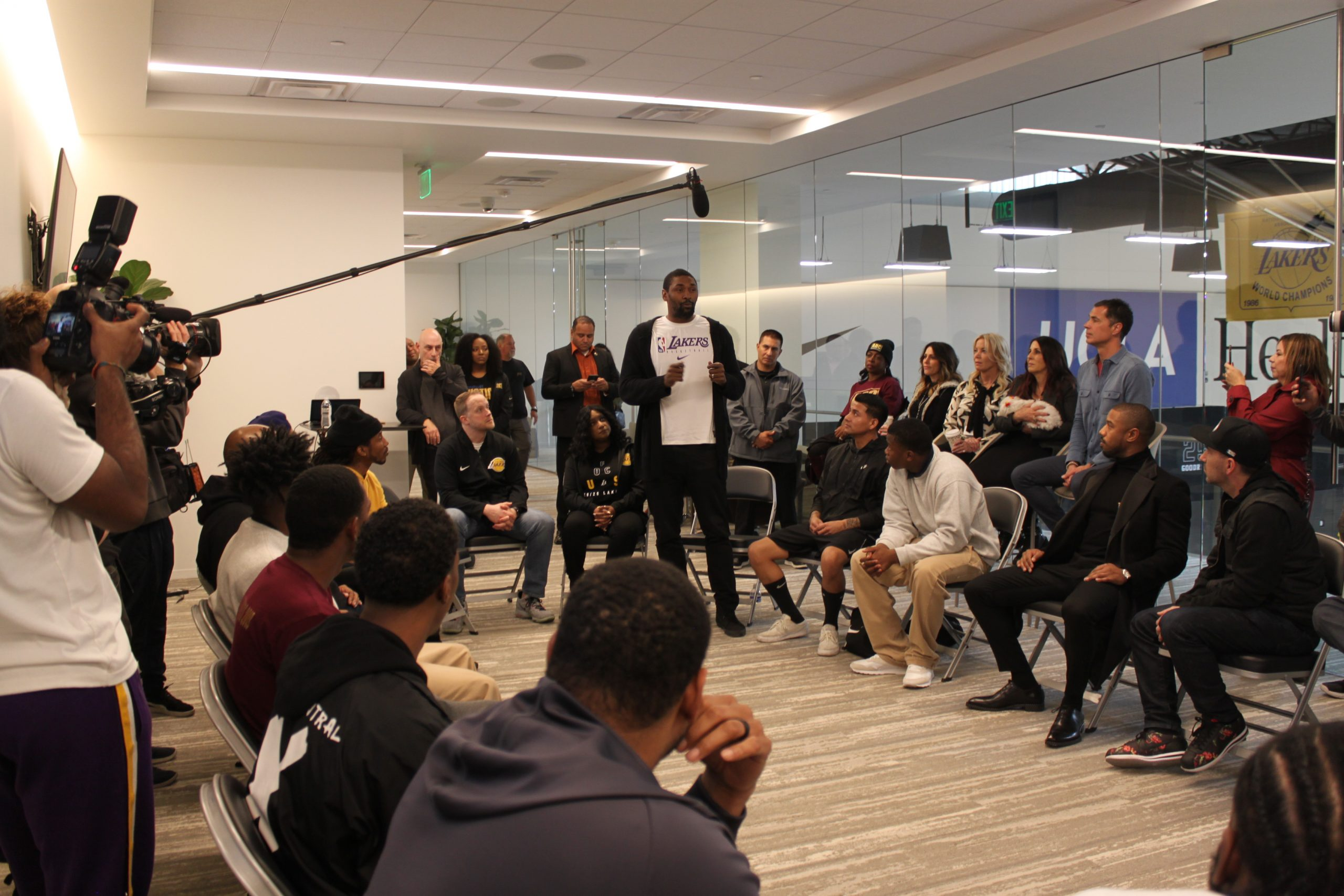 Youth offenders sit in a circle with professional basketball players.