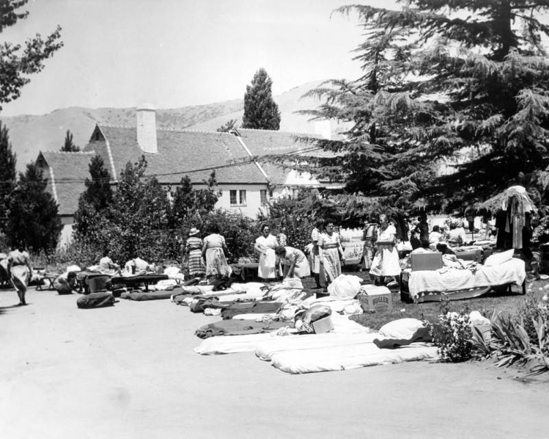Women camping outside unsafe prison buildings in 1952.