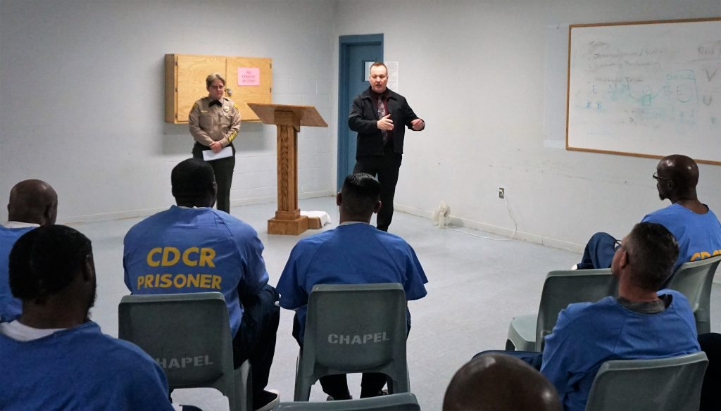 Correctional officer stands in the background while another man speaks to inmates at Kern Valley State Prison.