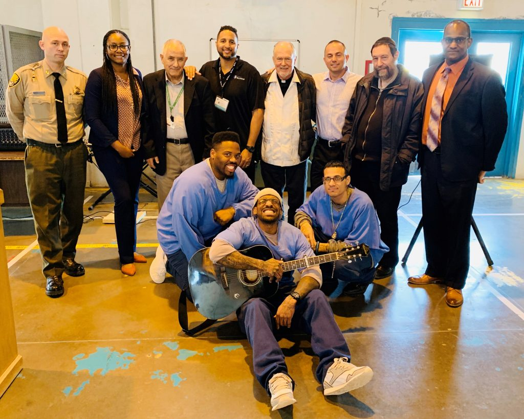 Three inmates sit on the floor while a group of prison staff stand behind them at CSP-Los Angeles County.