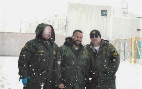 Three correctional staff smile while snow falls around them.