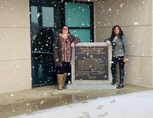 Two women stand beside a sign for the prison while snow is falling.
