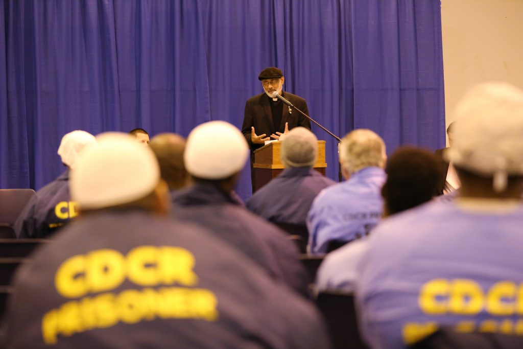 Mule Creek State Prison inmates and staff listen to a Catholic priest speak.