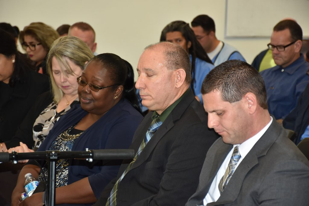 Mule Creek State Prison officials bow their heads in a moment of silence.