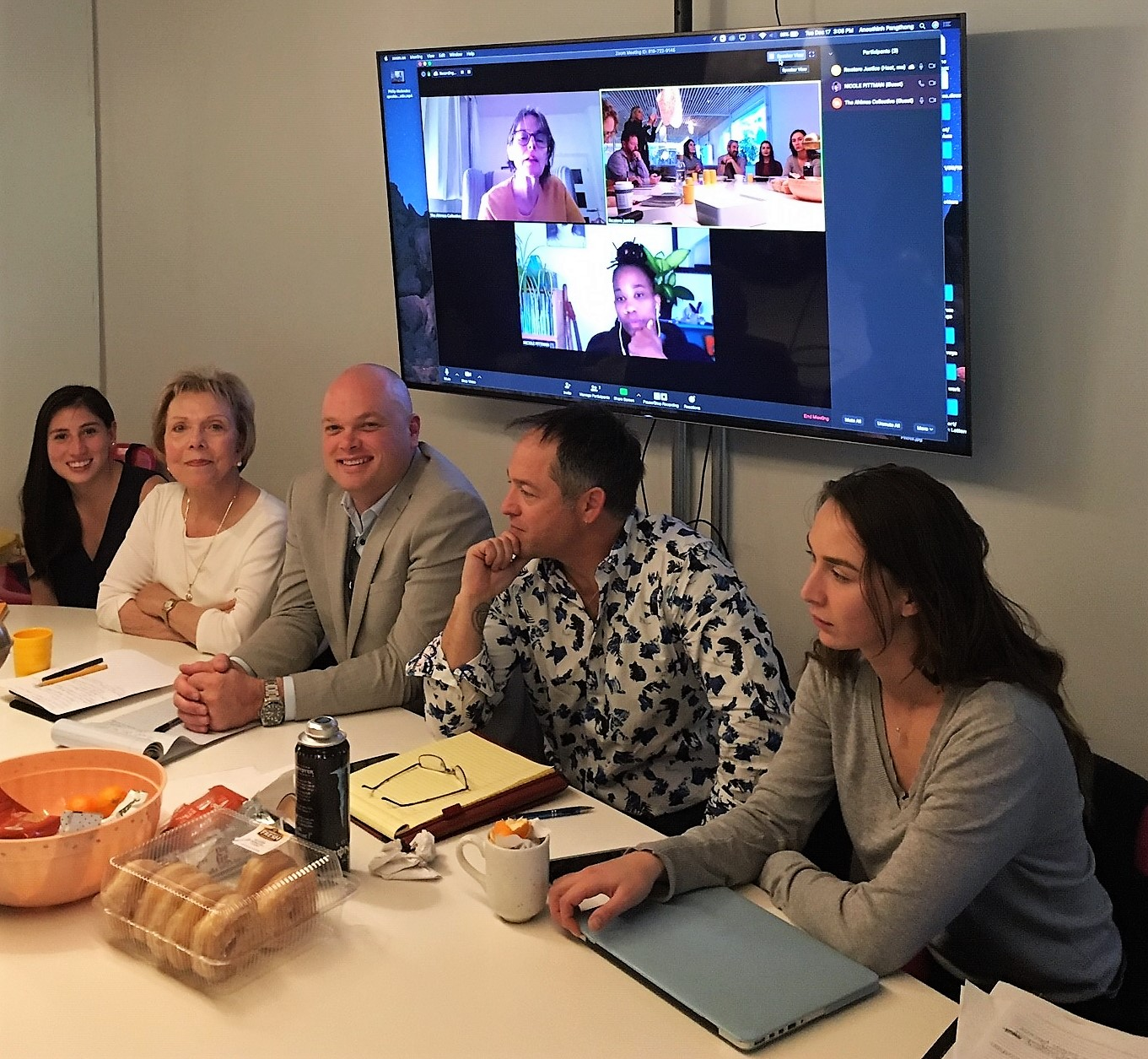 Men and women sit around a table while a video conference screen shows others participating.