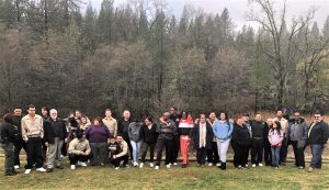 Fire camp inmates and family members pose for a photo with the forest as their backdrop.