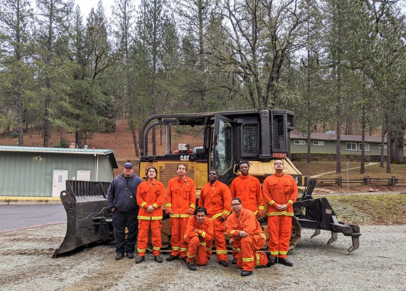 Seven inmate firefighters stand beside a large bulldozer.