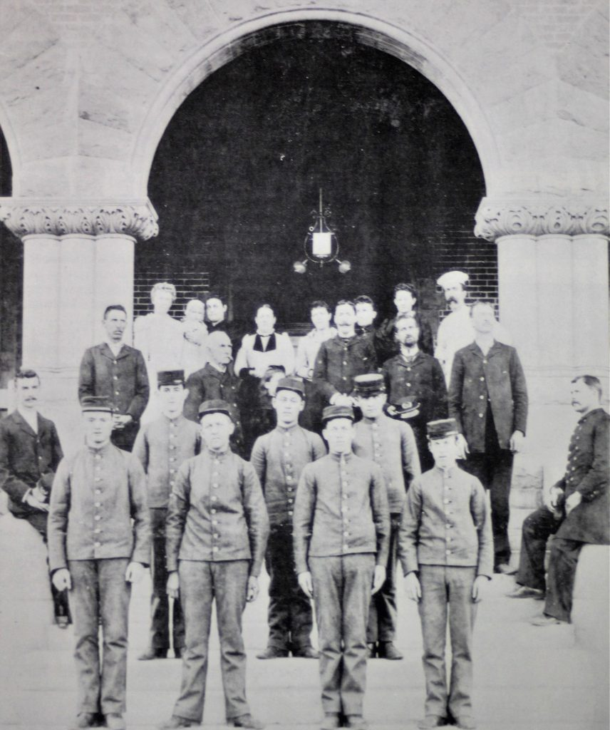 Seven young men in uniforms stand in front of Preston School of Industry staff.