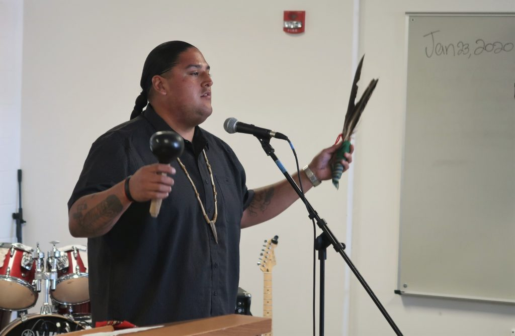 Man wearing necklace holds eagle feathers and speaks into a microphone.