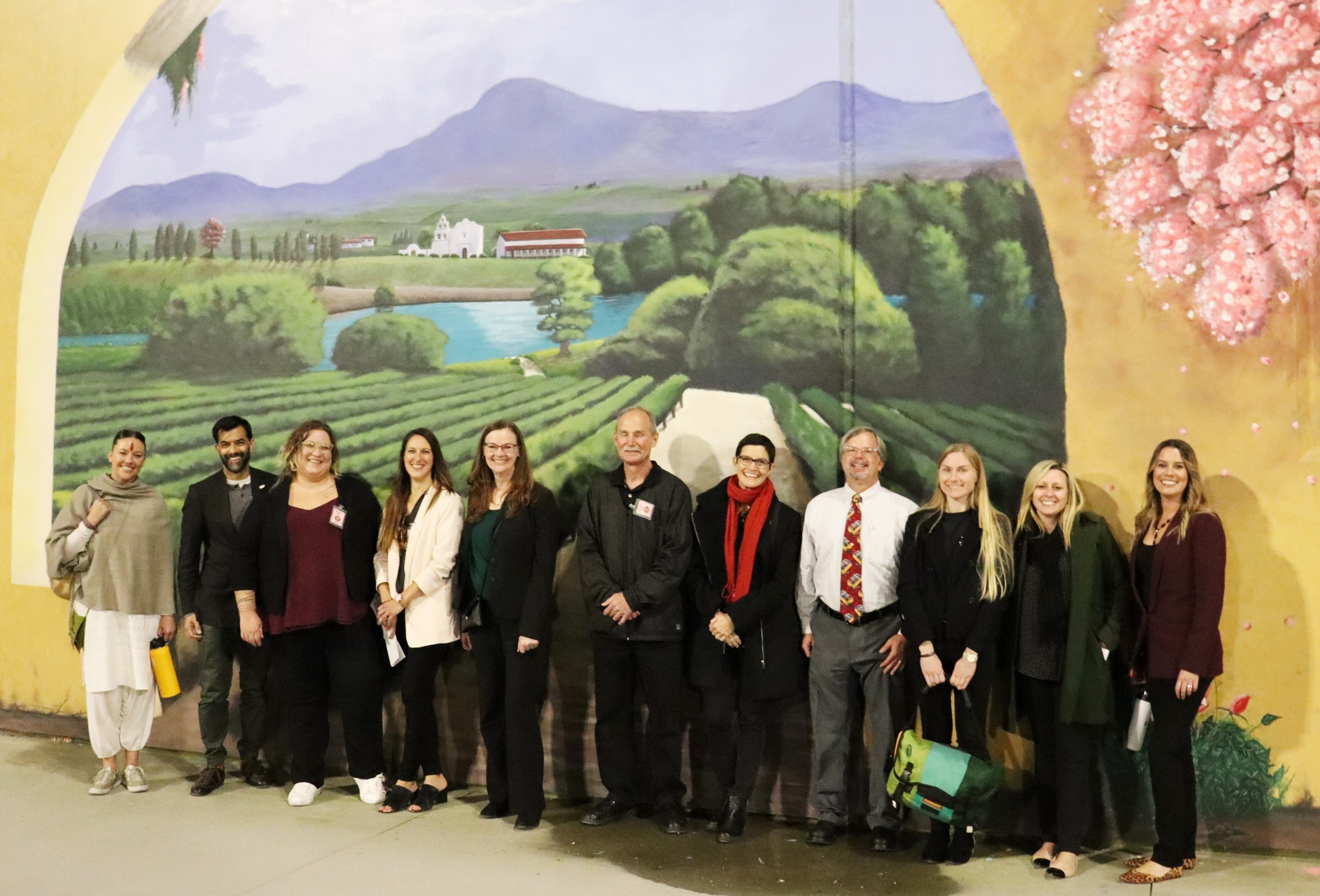 Men and women stand in front of a large mural depicting agriculture and a lake.