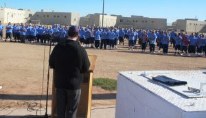 Back of chaplain at lectern addressing a group of prisoners who are standing