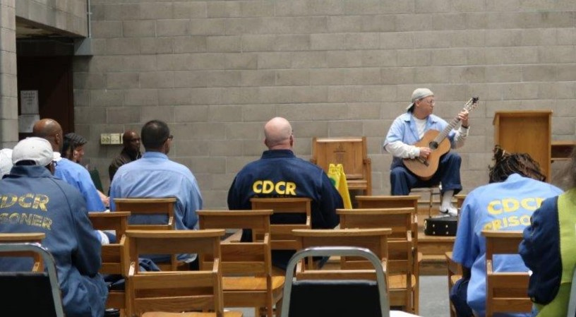 Inmate plays guitar on a stage in front of other inmates at California State Prison, Sacramento.