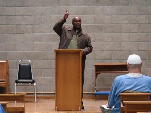 Man stands behind lectern, points upward, while speaking to inmates at California State Prison, Sacramento.