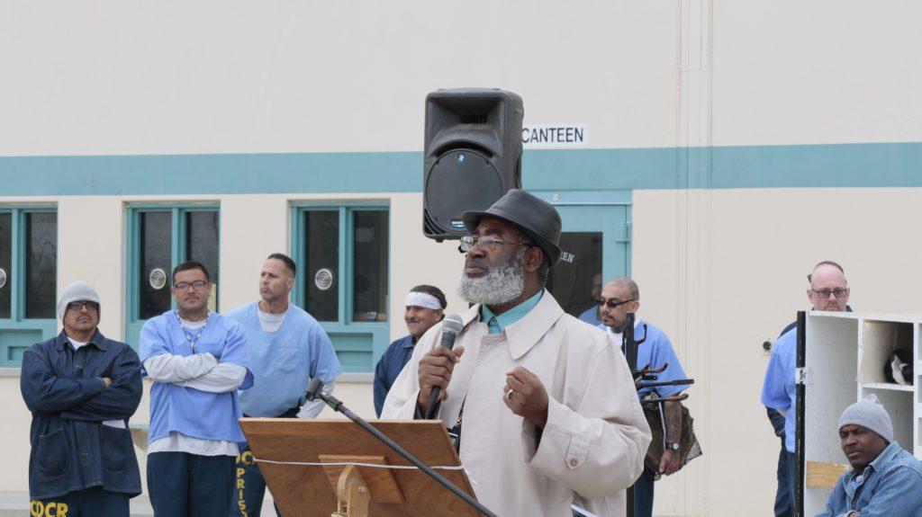 Man wearing a hat speaks to inmates at SATF.