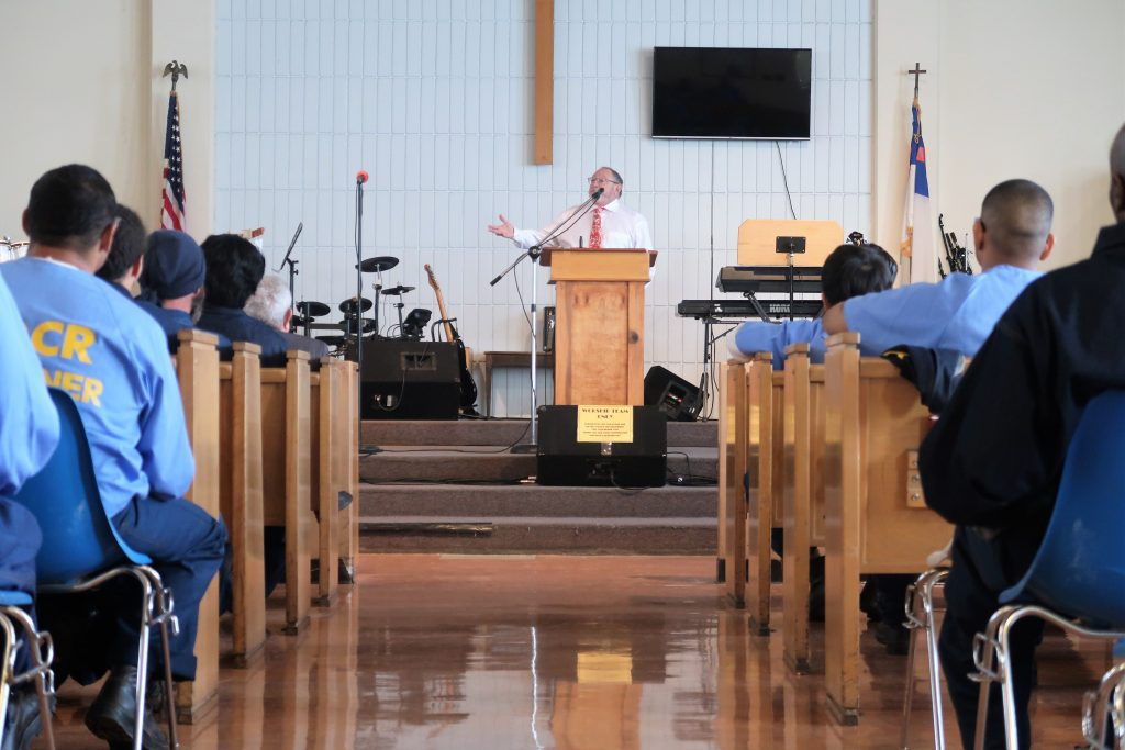 Prison chaplain speaks to inmates in a chapel.