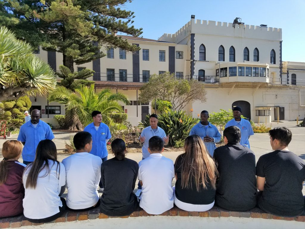 Students sit while five prison inmates talk to them in San Quentin.