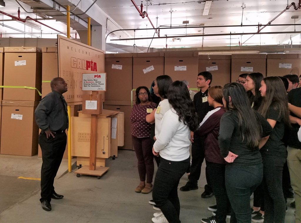 Boxes line the walls in a prison warehouse while students listen to a man speak about rehabilitation programs.