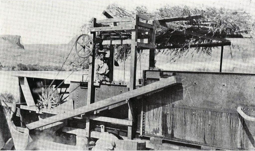 Man watches a machine process ore to capture gold.