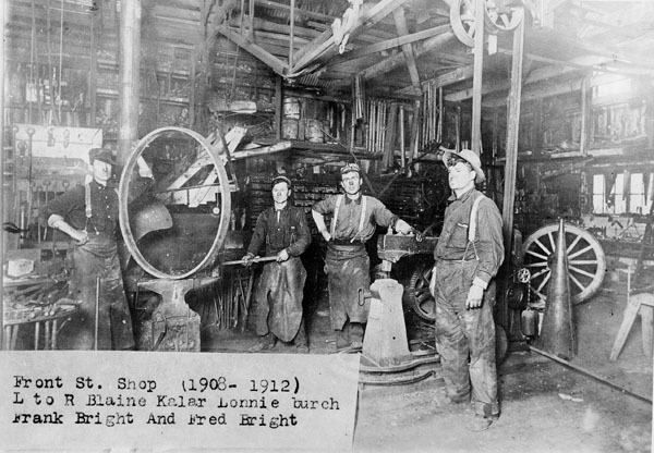 Men stand around old wagon wheels in a blacksmith shop.