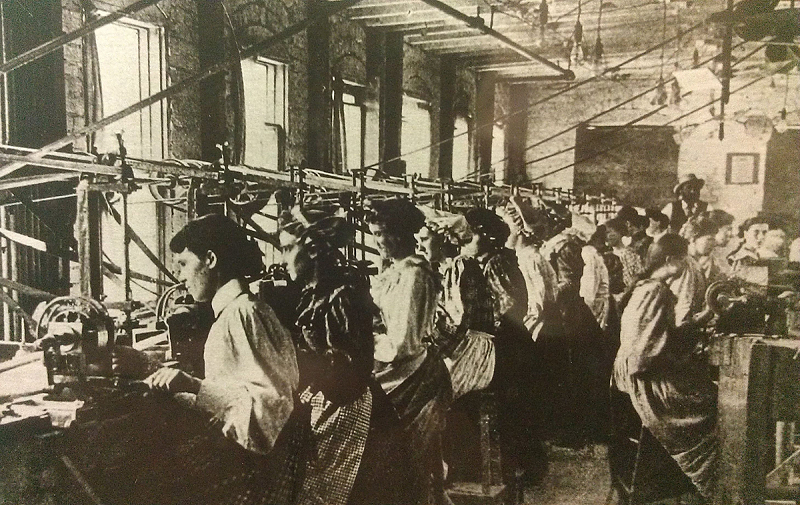 Women in a factory work machines to create buttons.