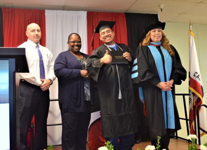 Two prison officials stand beside an inmate receiving a degree and a college superintendent.